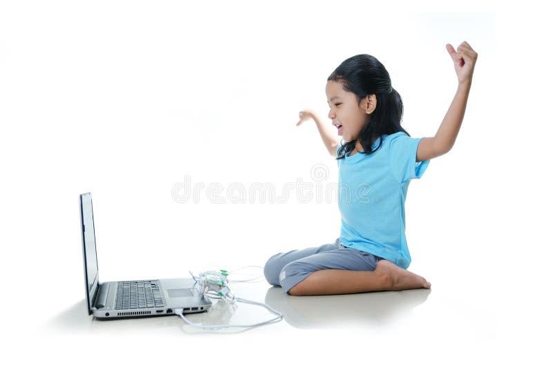 亚洲小女孩打与便携式计算机的比赛和joystic 库存图片