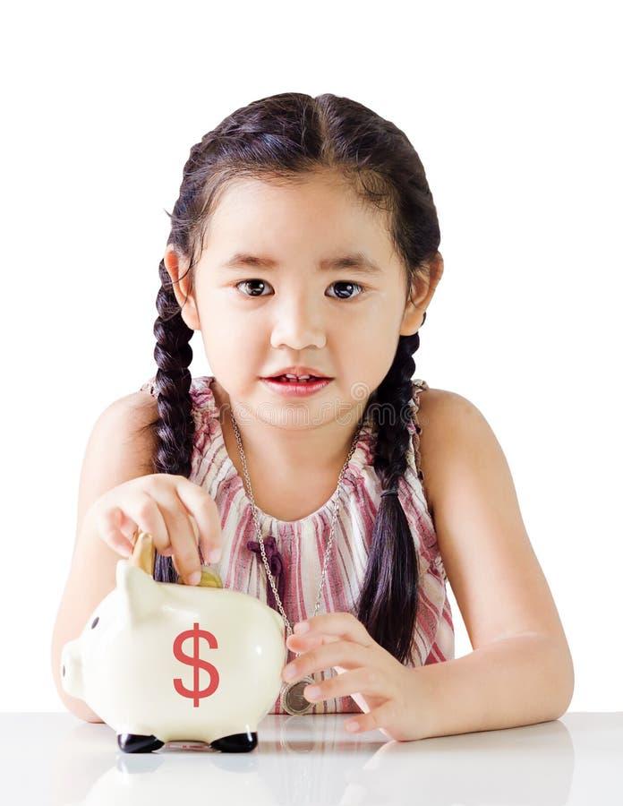 亚洲小女孩挽救金钱在存钱罐中 背景查出的白色 免版税库存图片