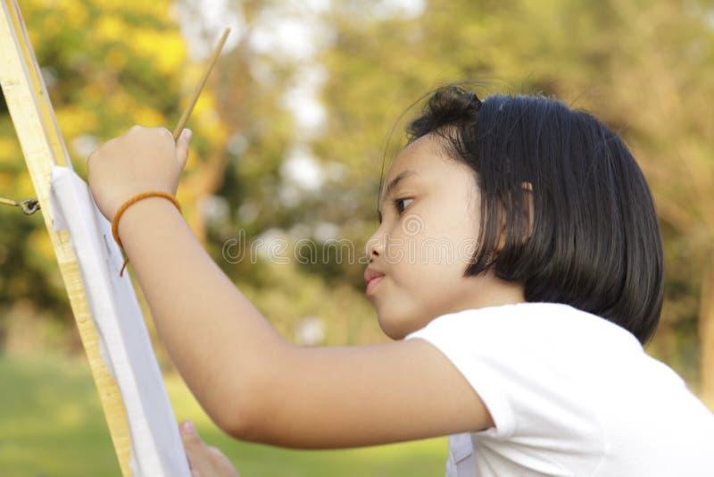 女孩绘画在公园 免版税库存图片