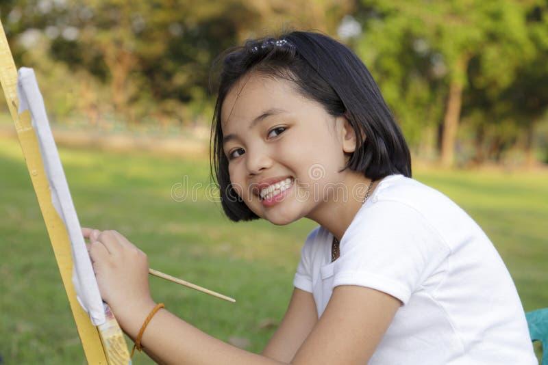 女孩绘画在公园 图库摄影