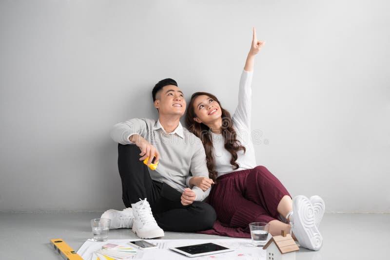 年轻亚洲成人夫妇坐计划新的家庭desig的弗洛尔 免版税图库摄影