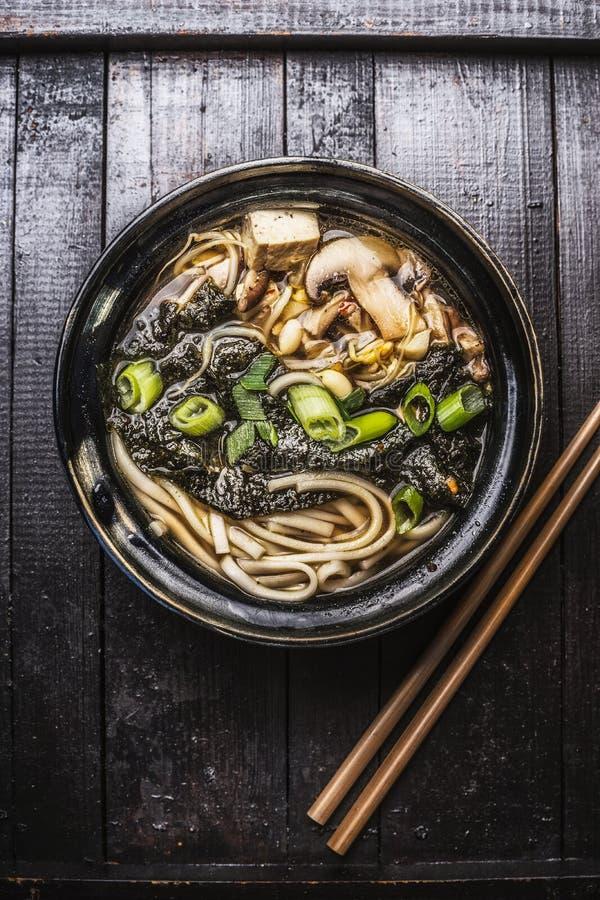 亚洲拉面汤用面条、豆腐和nori海草在碗有筷子的 免版税库存图片