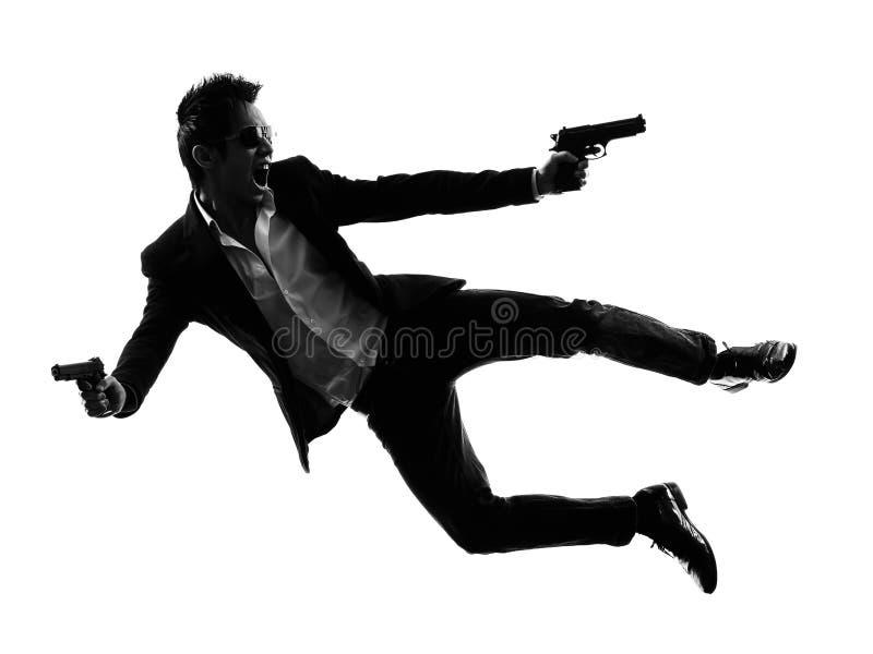 亚洲枪手凶手跳跃的射击剪影 库存照片