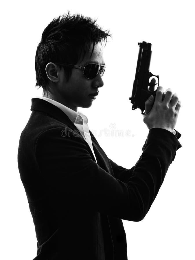 亚洲枪手凶手画象剪影 免版税库存照片