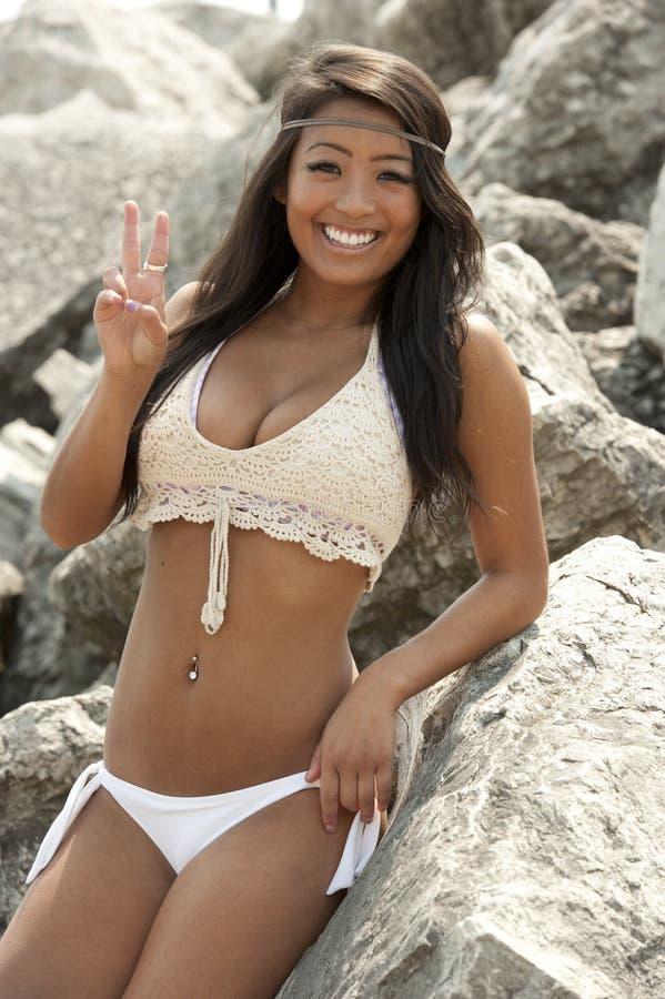 亚洲泳装式样笑与桃子标志 免版税库存照片