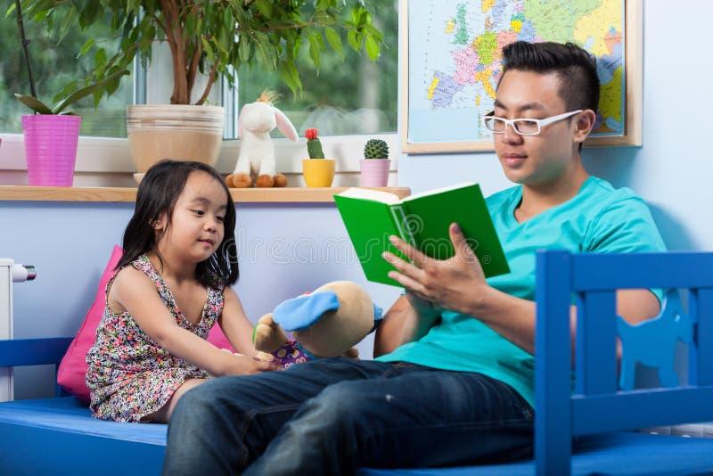 亚洲爸爸读书童话 图库摄影