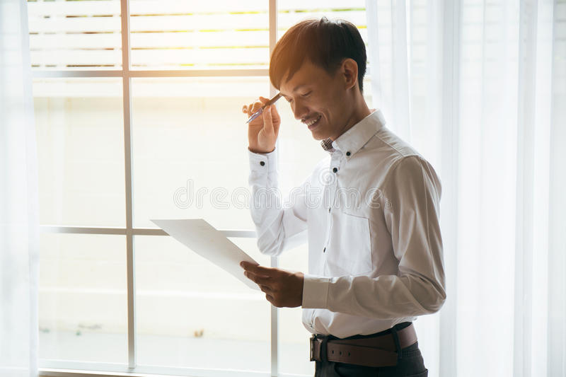 亚洲男性商人读书企业合同文件在私有工作室 图库摄影
