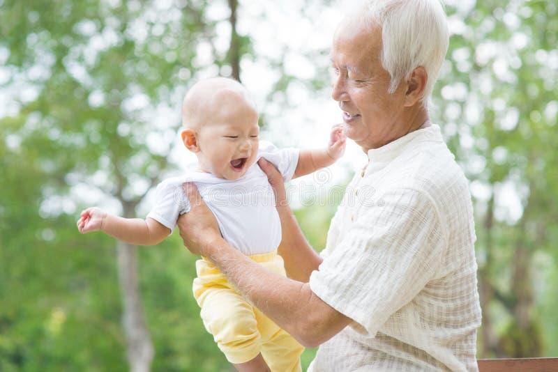 亚洲祖父使用与孙子 免版税库存照片