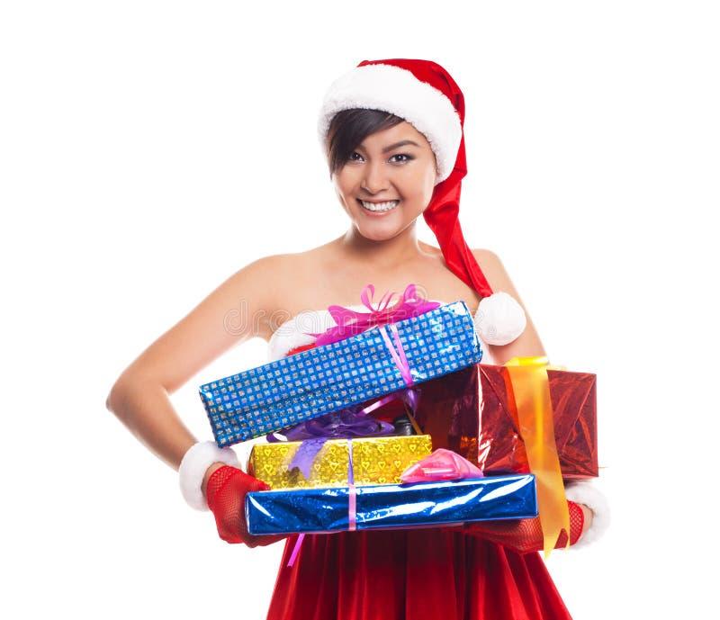亚洲背景美好的白种人圣诞节礼品帽子藏品查出混合模型纵向圣诞老人微笑的佩带的白人妇女 在whi的Iisolated 免版税库存照片