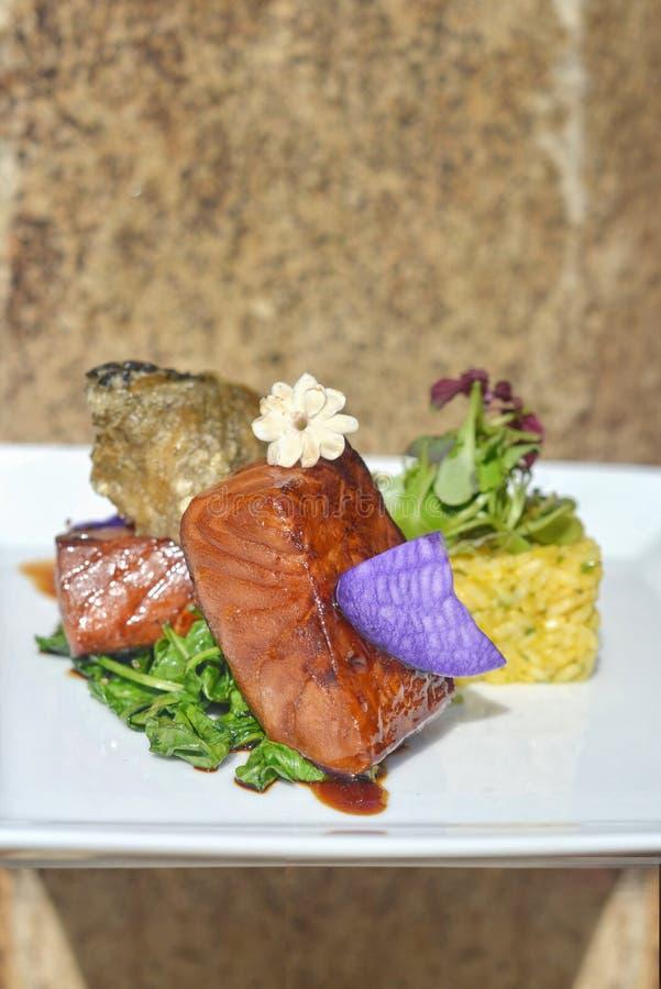 亚洲融合三文鱼、米和可食的花 免版税库存照片
