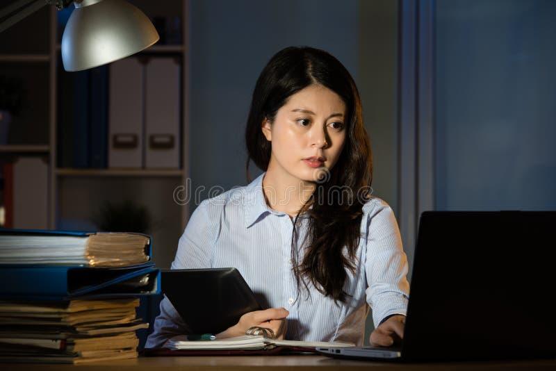 亚洲超时运转女商人用途数字式的片剂 免版税库存照片