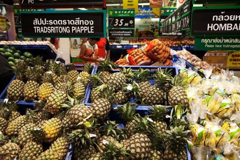 亚洲超级市场架子:堆菠萝、香蕉和其他果子 泰国和英国市场 免版税库存图片