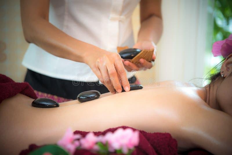 亚洲躺下在与传统热的石头的按摩床上的秀丽妇女沿脊椎在泰国温泉和健康中心,因此放松 免版税库存图片