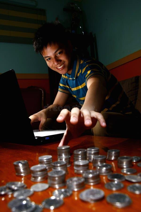 亚洲青少年在便携式计算机前面和到达堆的硬币 库存图片