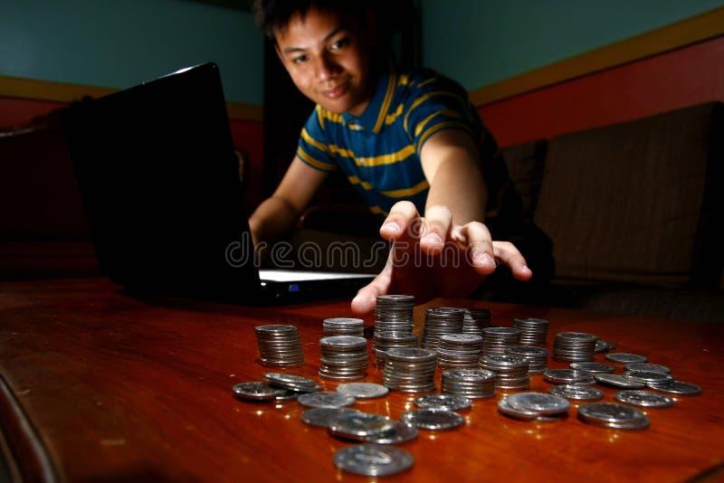 亚洲青少年在便携式计算机前面和到达堆的硬币 库存照片