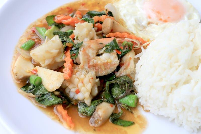 亚洲食物,混乱油煎了与辣椒酱和蓬蒿叶子的海鲜用在白色板材,辣辣椒泰国食物的米 免版税库存图片