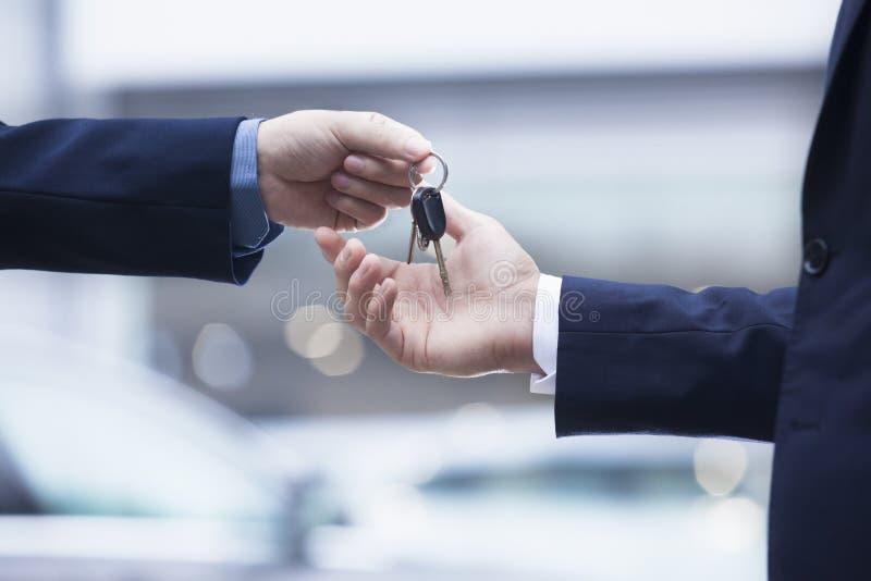 移交一辆新的汽车的汽车推销员钥匙给一个年轻商人,特写镜头 图库摄影
