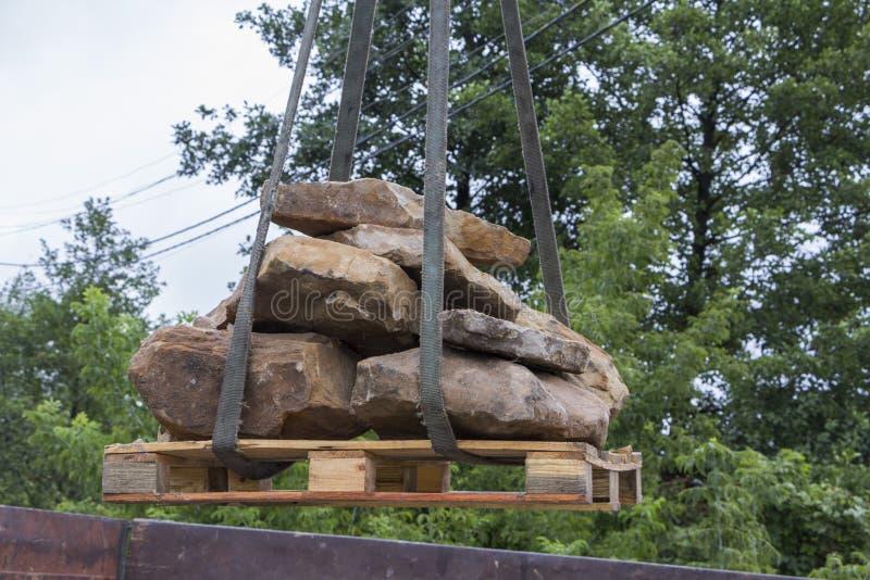 交付和卸载建筑石料用有起重机的卡车 库存图片