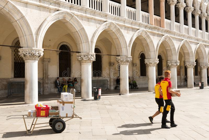交付在圣马可广场的敦豪航空货运公司邮差小包在威尼斯 库存图片