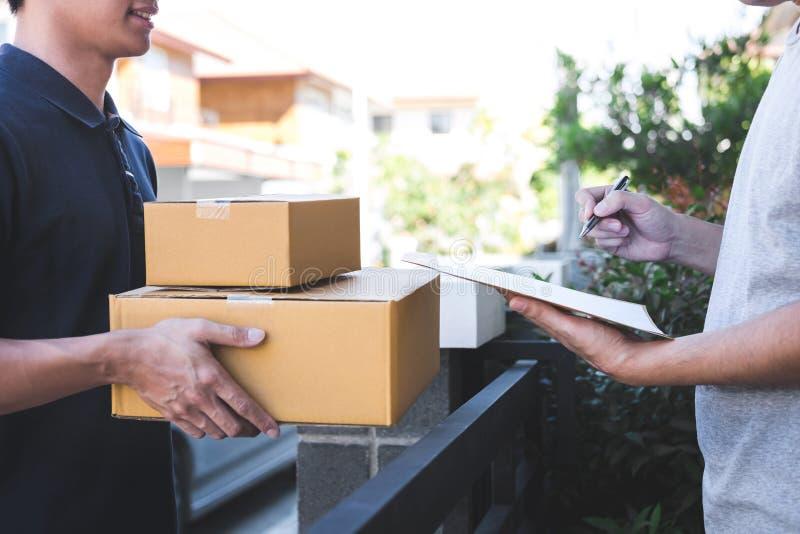 交付在家给小包箱子的邮件人接收者,年轻人签署的交货收据从岗位发货传讯者的包裹 免版税图库摄影