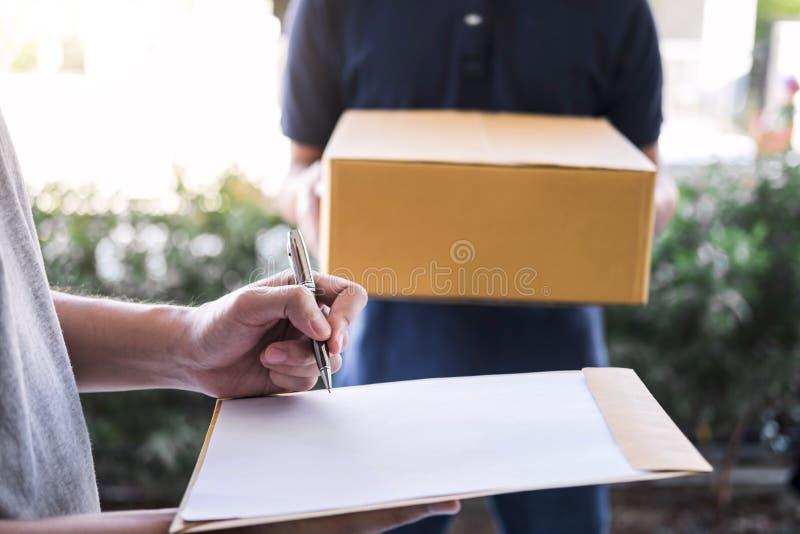 交付在家给小包箱子的邮件人接收者,年轻人签署的交货收据从岗位发货传讯者的包裹 图库摄影