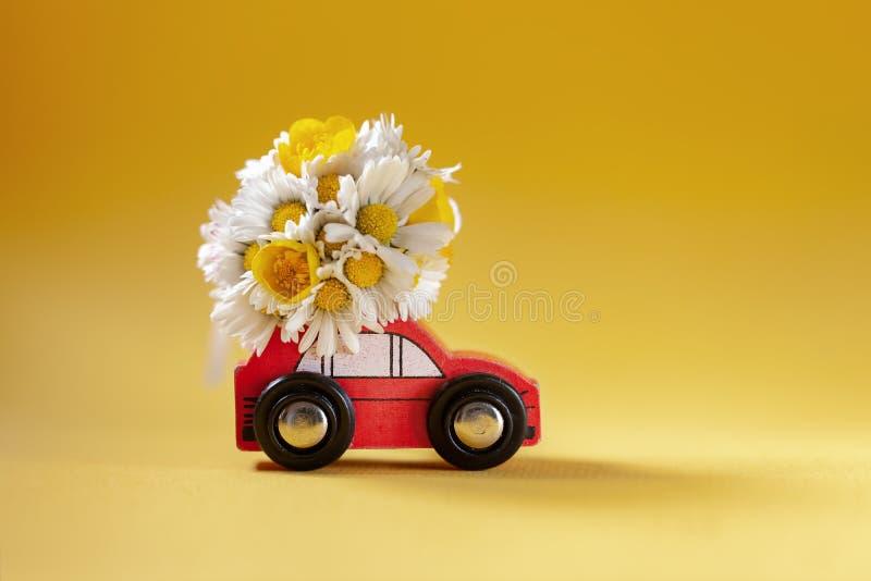 交付在黄色背景的红色玩具汽车花束箱子 E 愉快的妇女的天conncept 免版税库存图片