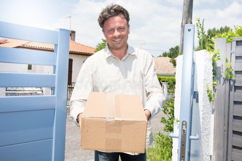 交付小包的微笑的送货人包装箱子给接收者 免版税库存照片