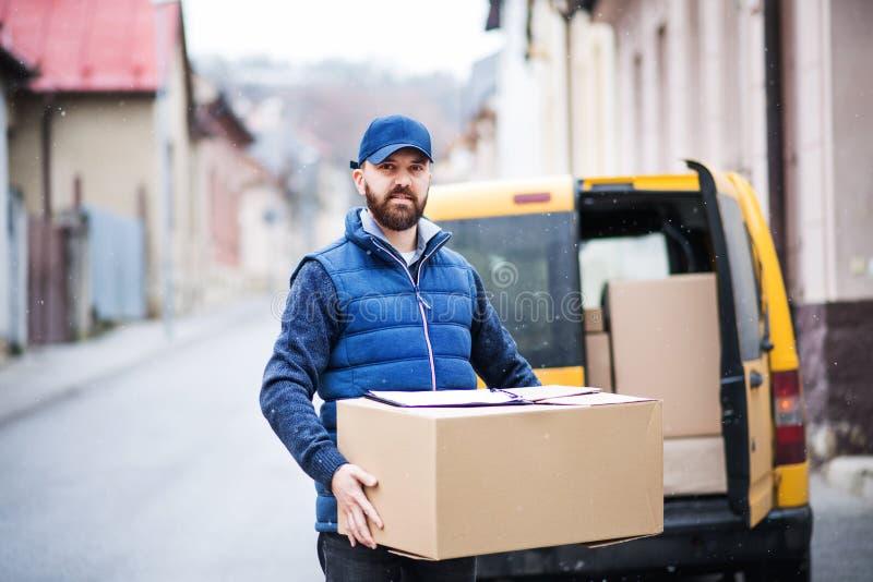 交付小包箱子的送货人到接收者 免版税库存图片
