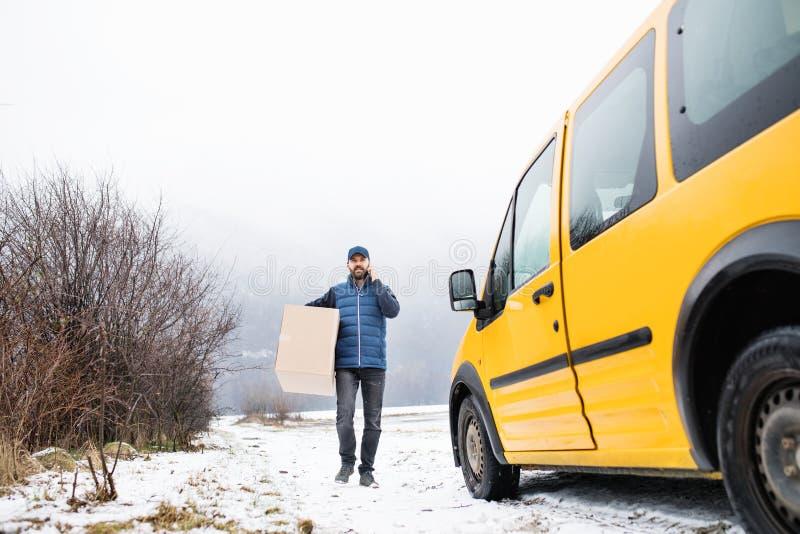 交付小包箱子的送货人到接收者 免版税库存照片