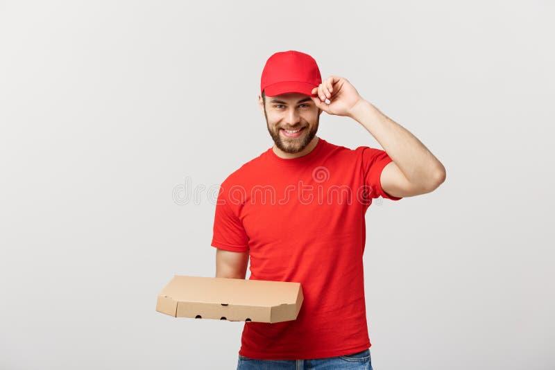 交付概念:拿着薄饼箱子的年轻haapy白种人英俊的薄饼送货人被隔绝在灰色背景 库存图片