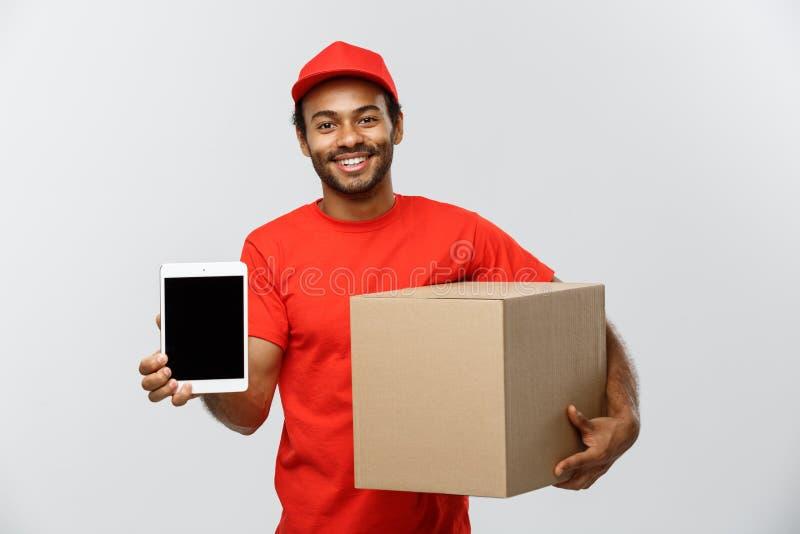 交付概念-英俊的非裔美国人的送货人或传讯者画象与显示片剂在您的箱子对检查 库存照片