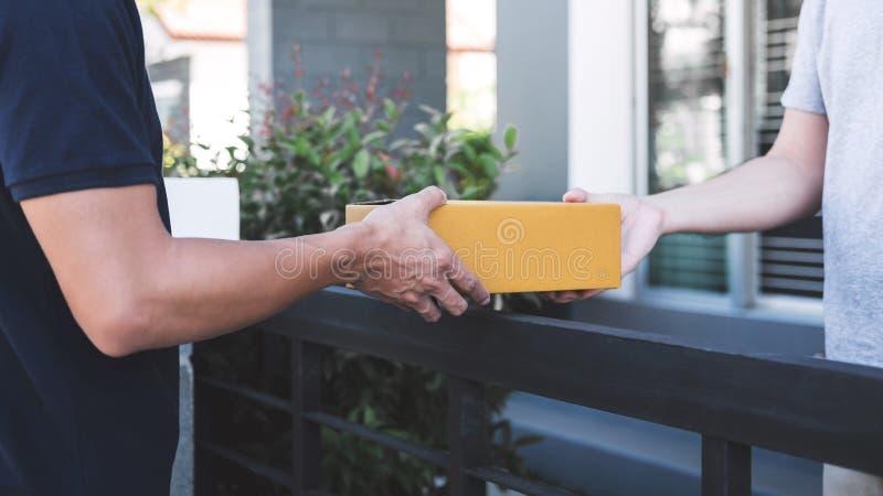 交付给小包箱子的邮件人接收者,年轻所有者接受从岗位发货,家的纸板箱包裹 库存图片