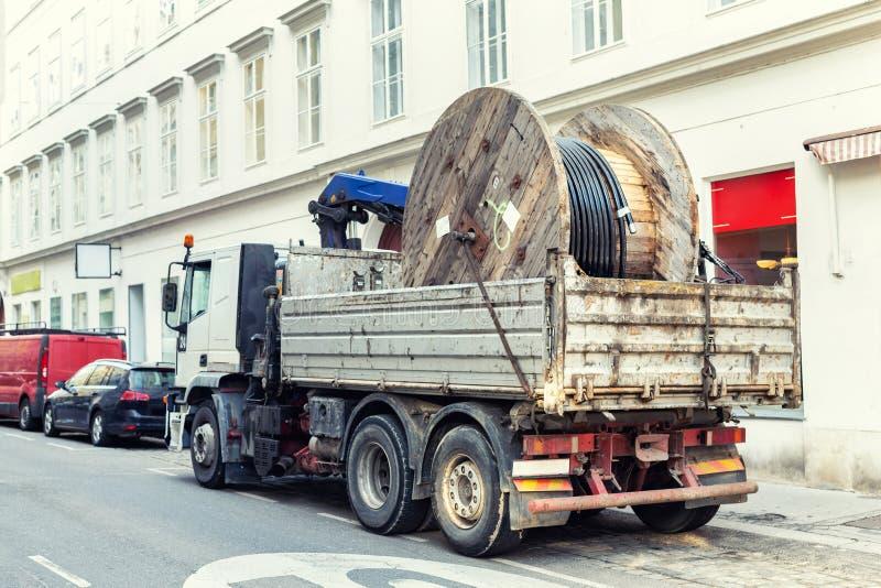 交付重的供应电缆卷轴的卡车在城市街道 免版税库存图片