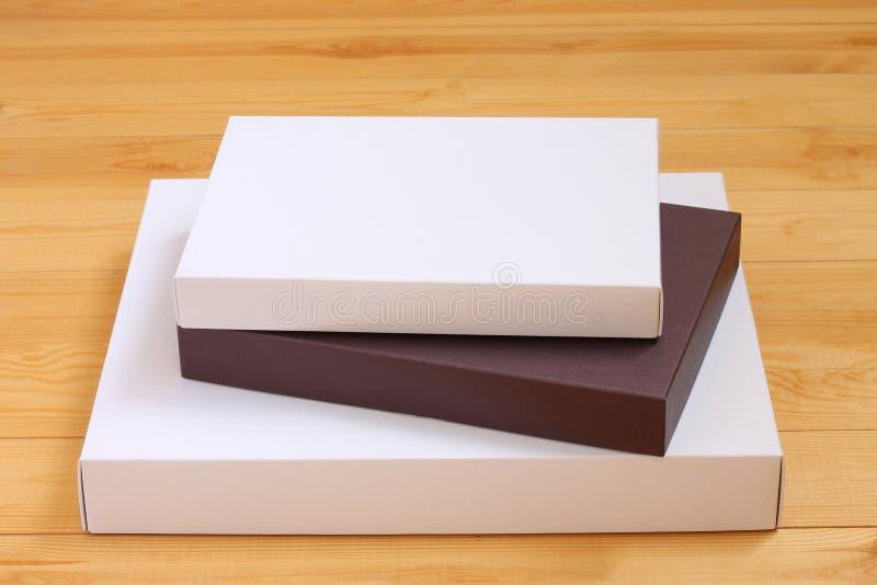 交付,移动,包裹和礼物概念-堆在木背景的纸板箱 节日礼物,传讯者交付 图库摄影