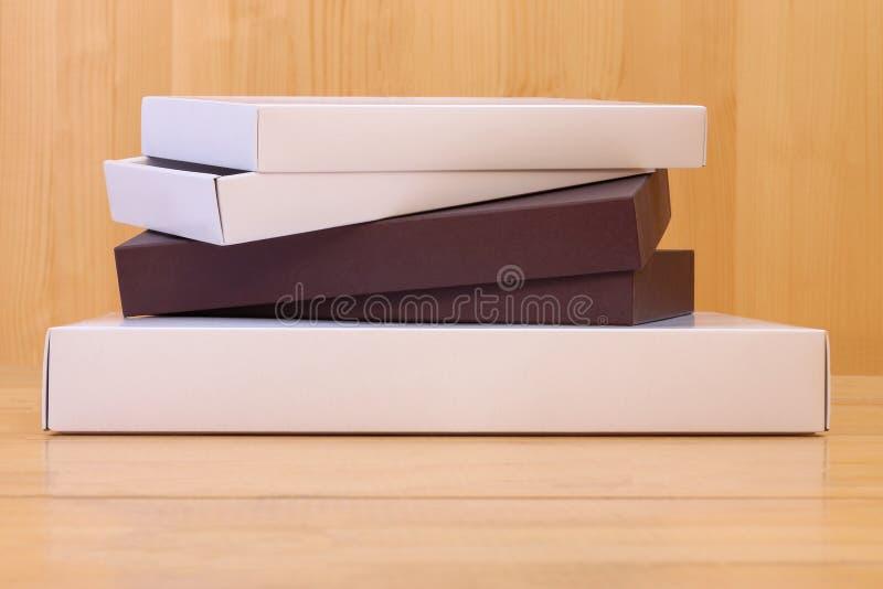 交付,移动,包裹和礼物概念-堆在木背景的纸板箱 节日礼物,传讯者交付 免版税图库摄影