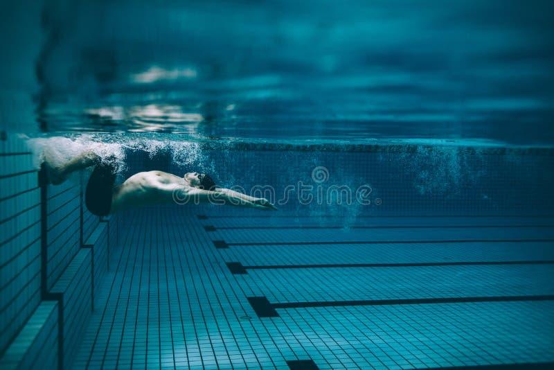 移交在游泳池的男性游泳者 免版税库存图片