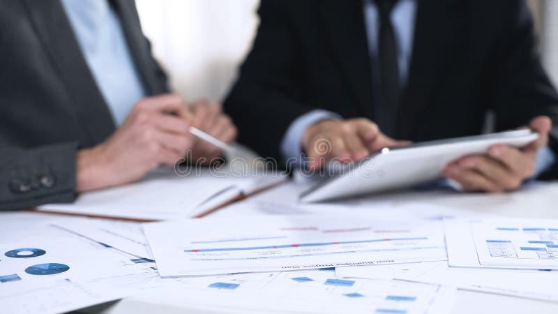 交换关于市场发展的商务伙伴想法,使用片剂个人计算机 库存图片
