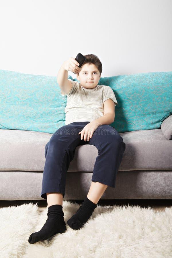 交换电视频道的男孩 免版税库存照片