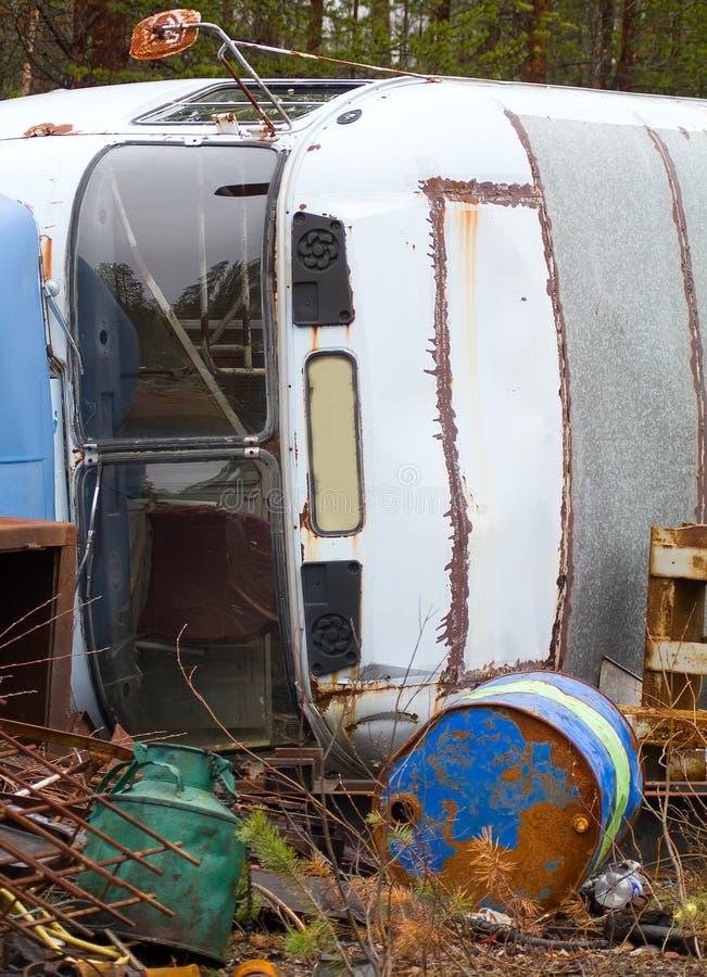 交换的转储的片段 老公共汽车和空的桶出于燃料 库存图片
