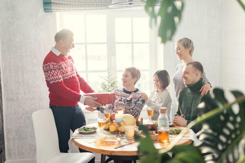 交换礼物的正面家庭在圣诞节 免版税库存照片