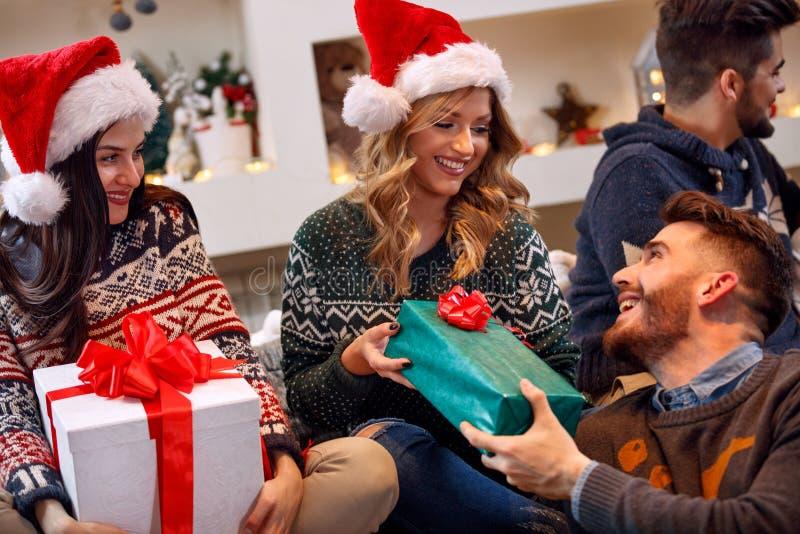 交换礼物盒的小组朋友在圣诞前夕 免版税库存图片
