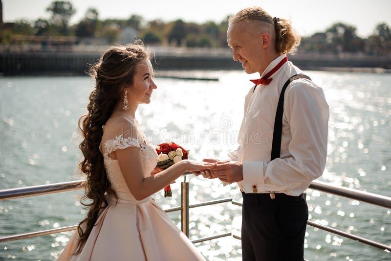 交换结婚戒指的年轻和愉快的已婚夫妇 免版税库存照片
