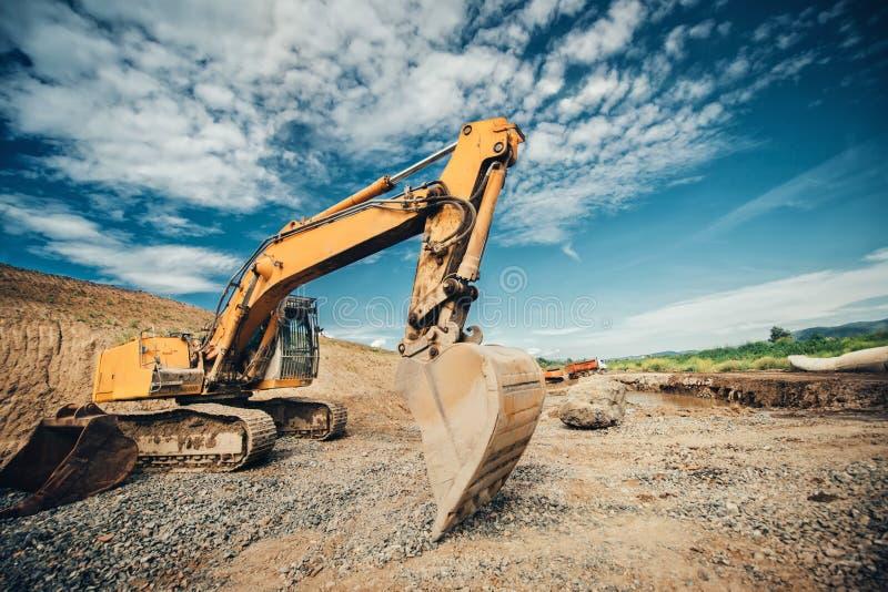 交换装载者、挖掘机有耐用瓢移动的地球的和装货倾销者卡车在长跑训练期间在高速公路 免版税库存图片