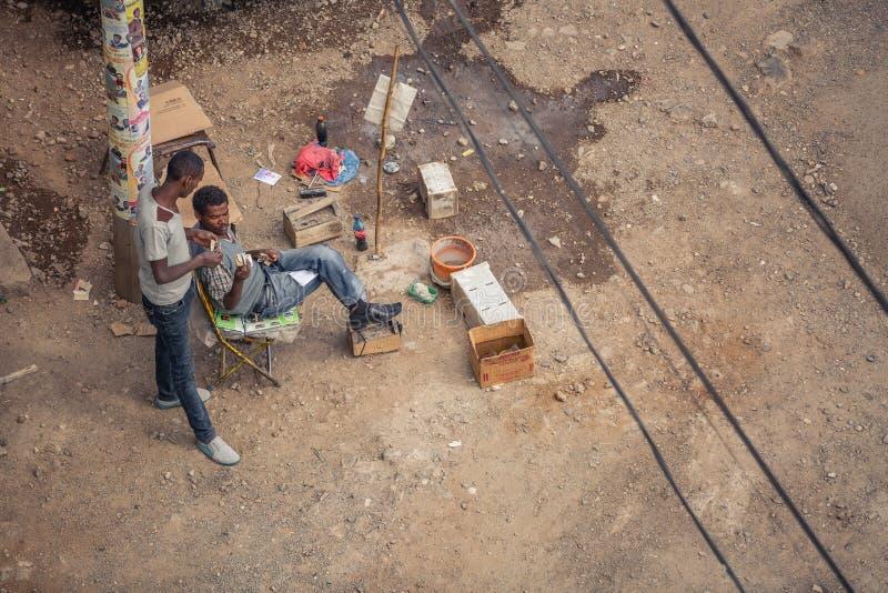 交换货币票据的两个人在鞋子亮光服务以后在贫困第三世界国家 免版税库存图片