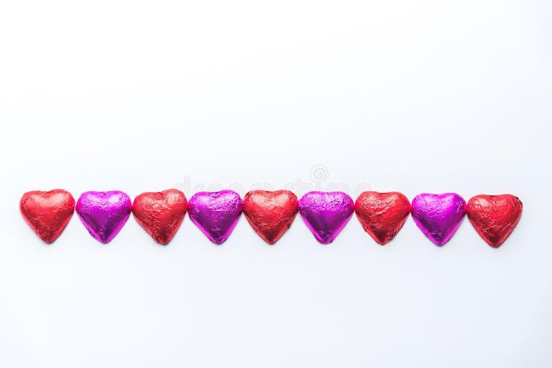 交替的桃红色和红色箔包装的巧克力心脏行在白色背景的 免版税库存图片