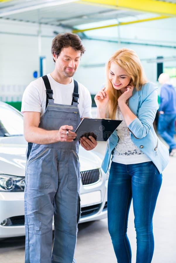 移交汽车的车间技工给客户 免版税库存图片