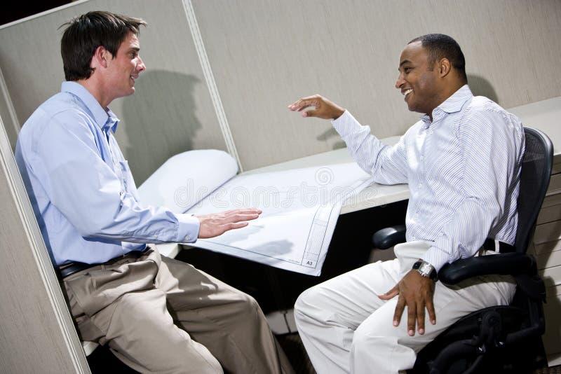 交谈的男性办公室工作者 免版税图库摄影