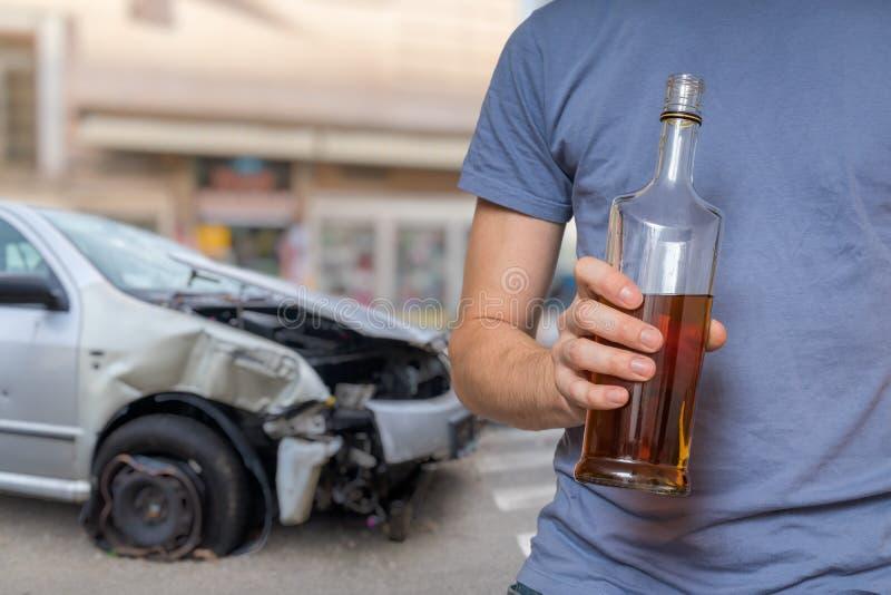 交通事故与酒精概念 酒驾手拿酒瓶 背景中的车祸 库存照片