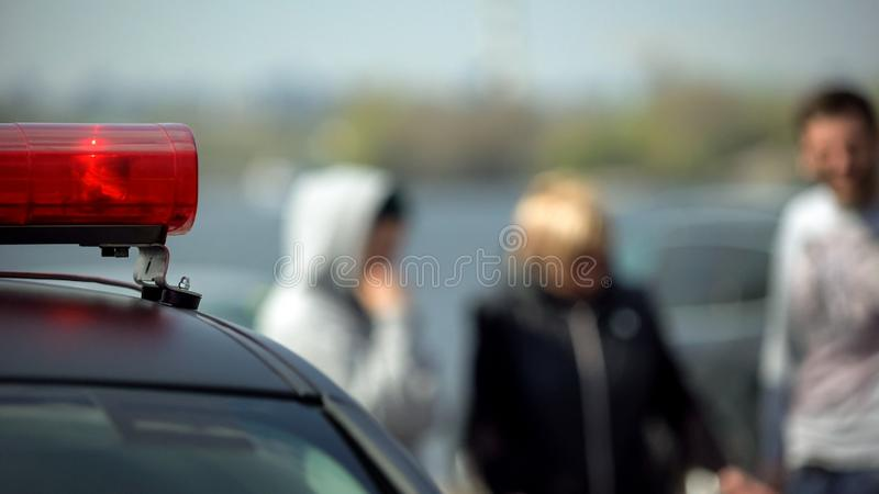 交通事故,站立在被碰撞的汽车警察光闪动附近的证人 免版税图库摄影