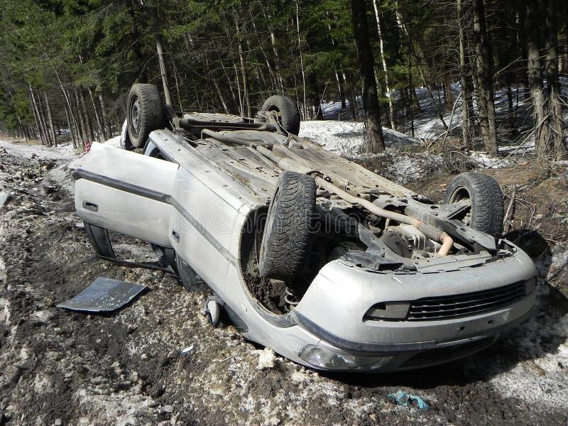 交通事故,被弄翻的汽车 事故在一条溜滑路的冬天发生了 免版税库存照片